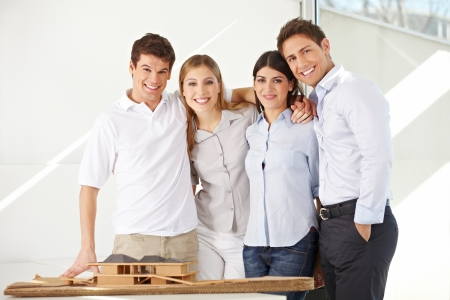 architectural studies: Happy team of architects with 3D house model in their office