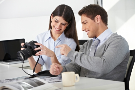 Man and woman sitting with camera in office and looking at photos photo