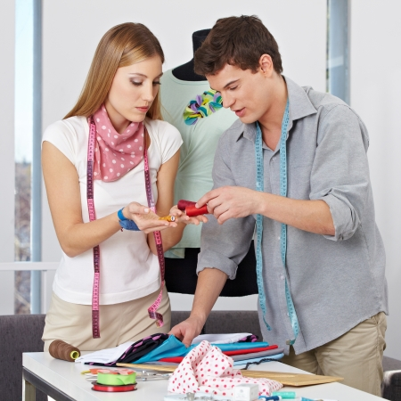 alteration shop: Two fashion designer choosing yarn in studio for their clothing collection Stock Photo