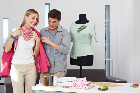 alteration shop: Two happy fashion designer doing a fitting in the studio Stock Photo