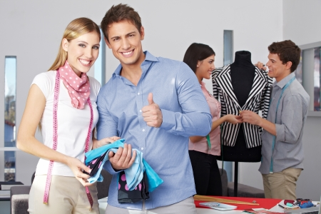 Fashion design student holding thumbs up with other people at work photo