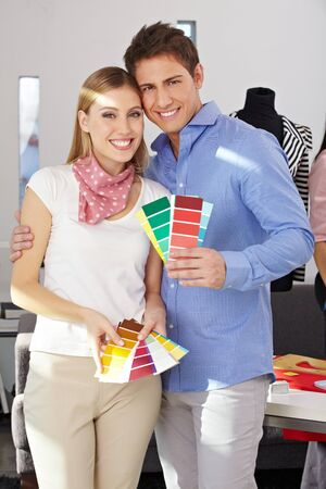 customer tailor: Young happy couple standing with color samples fan in studio