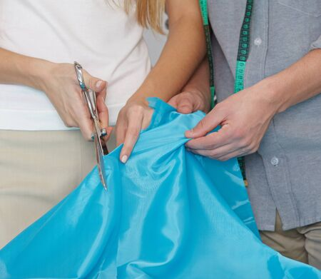alteration shop: Hands cutting blue fabric with dressmaker shear