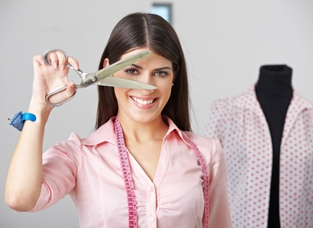 alteration shop: Happy fashion designer looking through open dressmaker shear