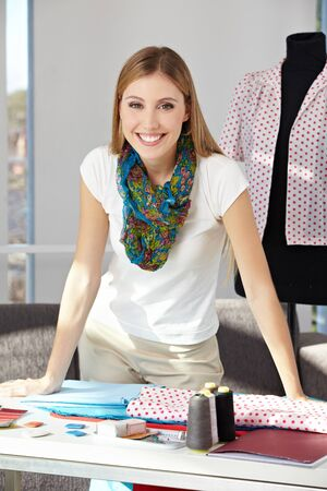 Happy fashion designer standing in her office with dress form Stock Photo - 15679673