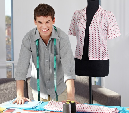 alteration shop: Happy custom tailor with tape measure in his studio Stock Photo