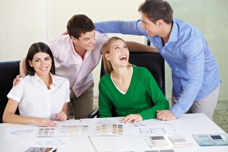 architectural firm: Two happy couples deciding house building materials on a desk