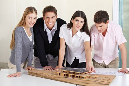 architectural studies: Team of architects standing around 3D building model in their office