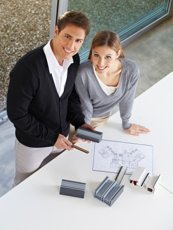 architectural firm: Happy couple looking at different window profiles for home renovation Stock Photo
