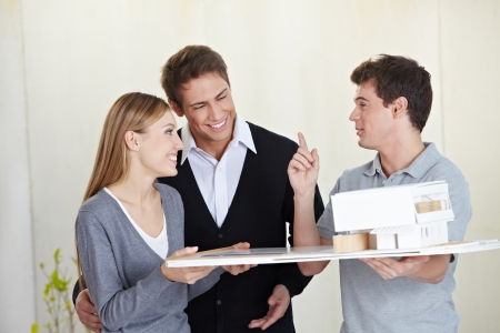 architectural firm: Architect showing 3D house model to smiling couple Stock Photo