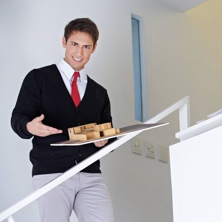 architectural firm: Happy Architect presenting house model on stairway