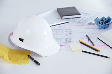 architectural firm: Blueprints, helmet and pens on the desk of an architect