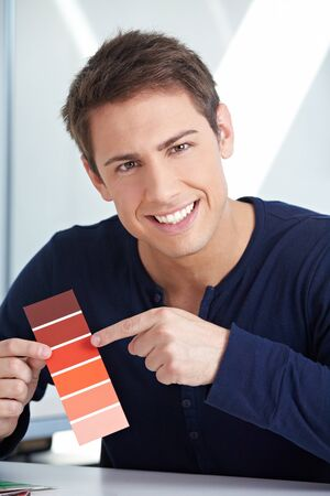 architectural firm: Smiling graphic designer with red color samples in his office Stock Photo