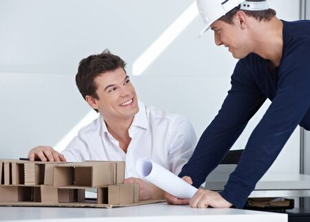 architectural firm: Architect with hardhat and blueprint talking to his employees in the office Stock Photo