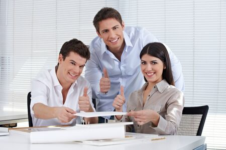 Three happy architects in their office holding the thumbs up photo