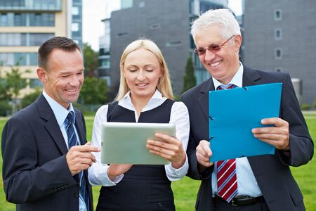 Happy business team working with tablet computer outdoors Stock Photo - 15719316