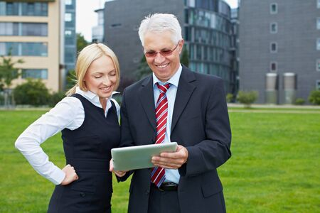 Two business people in a park looking at a tablet computer Stock Photo - 15719313