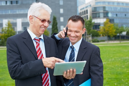 Two happy business men working outdoors with tablet computer and smartphone photo