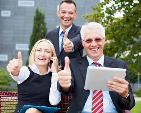 Happy business team holding their thumbs up with tablet computer in a park photo