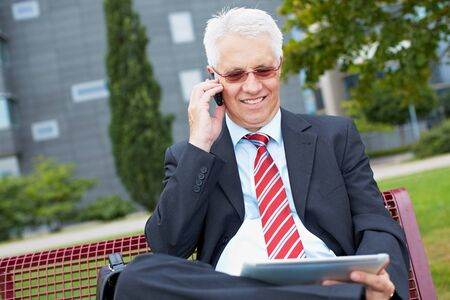 old business man: Senior business man working with tablet PC in a park Stock Photo