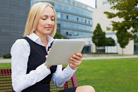 Attractive business woman outside holding a tablet PC Stock Photo - 15719301