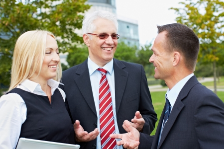 Three business people having a discussion outside in a park photo