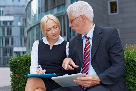 Two business people working with tablet computer outside the office Stock Photo - 15719310