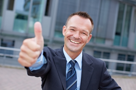 consent: Sucessful smiling business manager holding his thumbs up