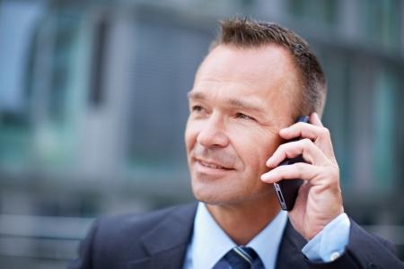 llamando: Hombre de negocios en la ciudad haciendo una llamada telefónica con el teléfono inteligente