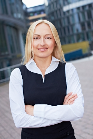 Portrait of happy attractive business woman standing outside the office photo