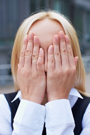 obscured face: Blonde business woman covering her face with her hands Stock Photo