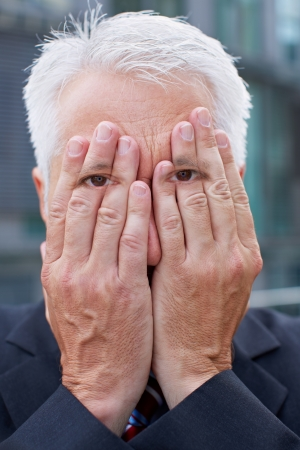 Elderly manager with eyes on hands covering his face