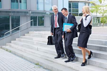 Three business people descending a stairway and talking photo