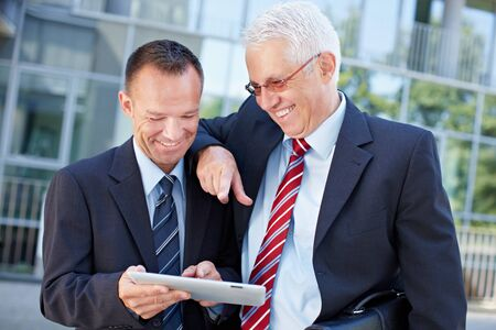 Two happy business men working together on a tablet computer Stock Photo - 15719320