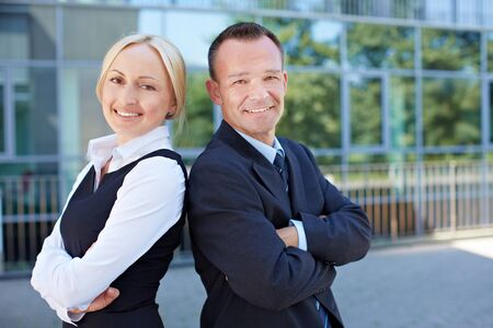 Business man and smiling woman leaning back on back outside the office photo