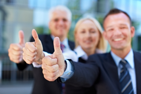 thumbs up symbol: Happy successful business group holding their thumbs up