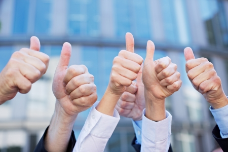 team victory: Many thumbs of different business people pointing up