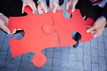 business puzzle: Many hands holding two red jigsaw puzzle pieces