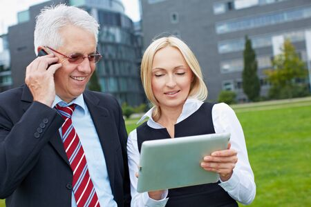 Two business people with smartphone and tablet PC outdoors photo
