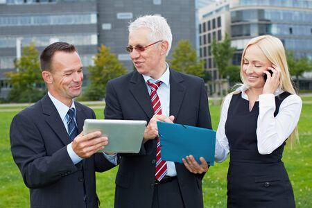 Happy business people team working together with tablet PC in a park photo