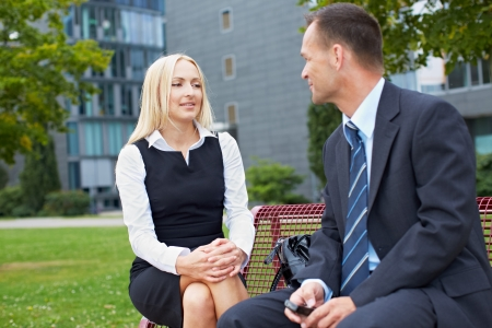 Two business people talking outside on a park bench photo