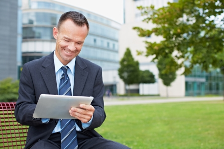 shopkeeper: Happy business man using tablet PC outside on a park bench