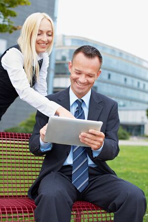 Man and business woman working with tablet computer in a park Stock Photo - 15784011