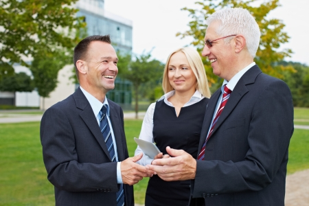 Three happy business partner people talking outside photo