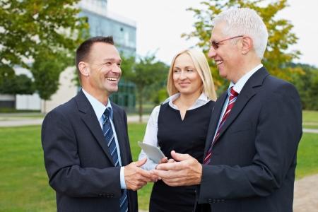 Drei glückliche Geschäftspartner Leute reden außerhalb