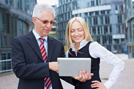 Business man and woman looking together at a tablet PC Stock Photo - 15784022