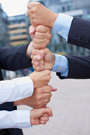 Many business people building a tower of their clenched fists photo