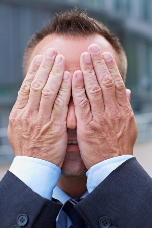 coward: Business man covering his face with his both hands