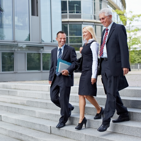 Three happy business people walking together outside photo