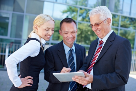 Business team looking together at a tablet computer Stock Photo - 15784030